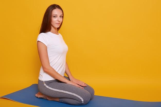 Foto della ragazza esile che si siede nella posizione di virasana e che medita a casa