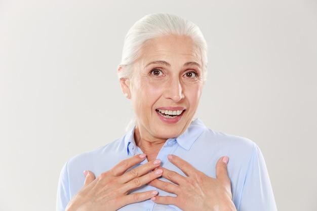 Foto della signora anziana sorpresa con le mani sul suo petto