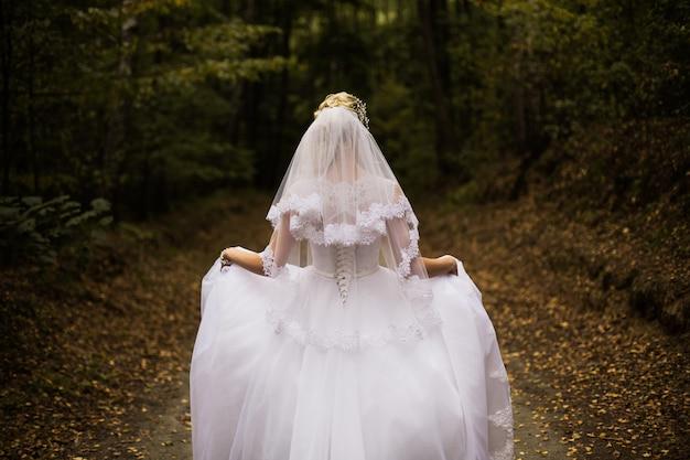 Foto della sposa dal retro, abito da sposa su una ragazza, la sposa nella foresta, la principessa nella foresta, abito da sposa dalla parte posteriore sulla donna, abito a orlo, velo, servizio fotografico di nozze, acconciatura