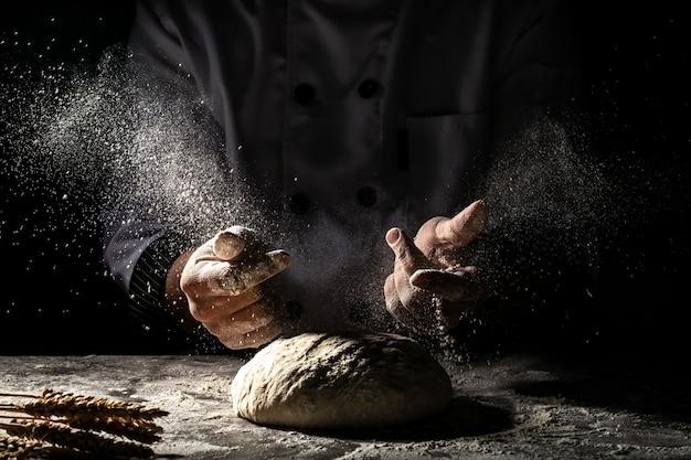 Foto delle mani degli uomini e della farina con la spruzzata della farina