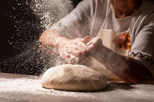 Foto delle mani delle donne e della farina con la spruzzata della farina. cucinare il pane. impastare la pasta. isolato su sfondo scuro spazio vuoto per il testo