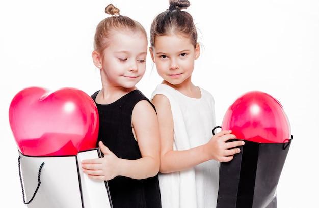 Foto di 2 bambine con abiti eleganti che tengono grandi borse con all'interno palloncini a forma di cuore