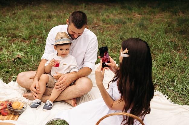 Foto di allegra mamma caucasica, papà e il loro bambino si divertono insieme e sorridono in giardino