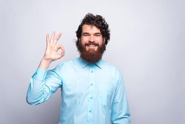 Foto di allegro giovane barbuto che indossa camicia blu e che mostra il gesto giusto.