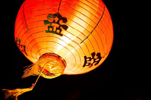 Foto di appendere lanterna rossa cinese nella vicina. tradizionale lampada rossa orientale.