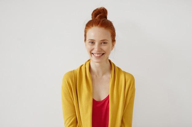 Foto di attraente adorabile giovane donna dai capelli rossi con le lentiggini vestita casualmente, sorridendo ampiamente, felice con una buona notizia.