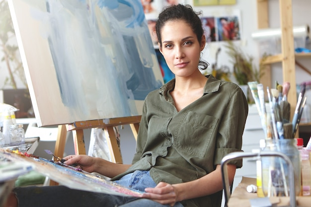 Foto di attraente giovane femmina caucasica professionale in abiti casual tenendo la tavolozza e il coltello da pittura lavorando su pittura ad olio, mescolando i colori, avendo ispirato espressione sul suo viso