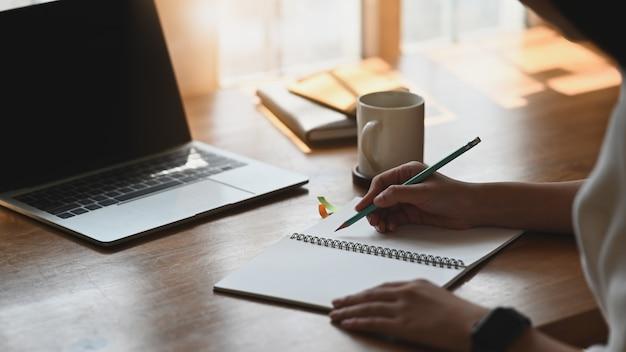 Foto di bella donna che lavora come scrittore prendendo appunti mentre era seduto di fronte un computer portatile che mettendo sul tavolo di legno con tazza di caffè e taccuino. concetto di composizione / poeta / scrittore.