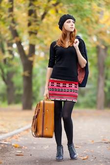 Foto di bella giovane donna con la valigia sui precedenti meravigliosi del parco di autunno