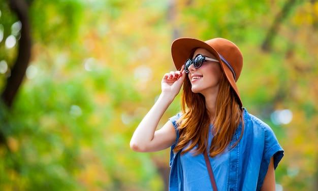 Foto di bella giovane donna in piedi sul meraviglioso parco in autunno
