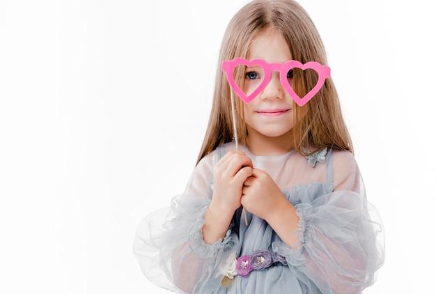 Foto di bella ragazza con un vestito grigio e occhiali di cartone a forma di cuori