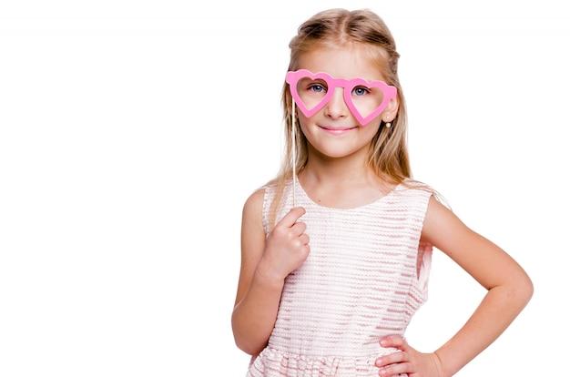 Foto di bella ragazza con un vestito rosa e occhiali di cartone a forma di cuori