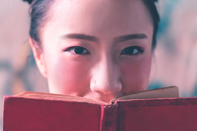 Foto di bella signora cinese che copre il viso con il libro rosso.