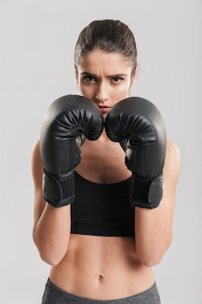 Foto di bella sportiva bruna allenamento in guantoni da boxe e guardando, sul muro bianco