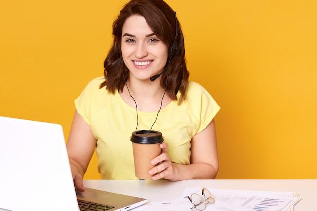 Foto di bello giovane operatore di call center che posa contro il giallo mentre sedendosi allo scrittorio bianco con le cuffie