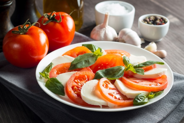 Foto di caprese insalata con pomodori, basilico, mozzarella, olive e olio d'oliva