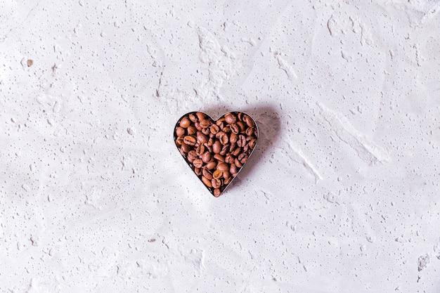 Foto di chicchi di caffè a forma di cuore copia spazio su sfondo concreto. foto orizzontale. vista dall'alto