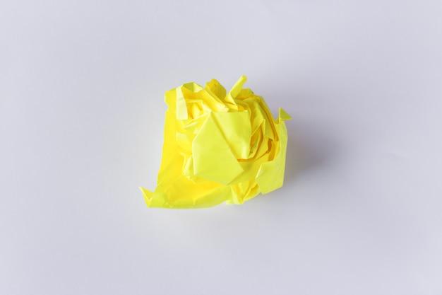 Foto di concetto della palla di carta gialla sgualcita su fondo bianco. mancanza di idee, sofferenze creative. sovraccarico di carta, protezione dell'ambiente