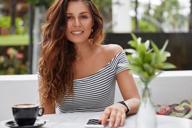 Foto di donna rilassata dall'aspetto piacevole nell'accogliente caffetteria