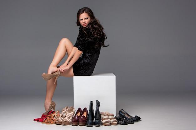 Foto di donna seduta cercando su scarpe col tacco alto