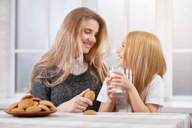 Foto di due sorelle ridenti, più giovani e più odierne. entrambe le ragazze hanno i capelli lisci biondi.