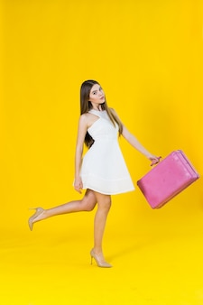 Foto di estate di bella donna bionda con la valigia rosa