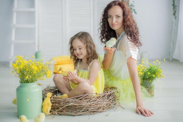 Foto di famiglia di mamma e figlia in abiti luminosi gialli contro un muro bianco.