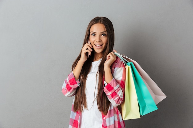 Foto di felice eccitata giovane donna sorprendente, tenendo le borse della spesa mentre parla al telefono