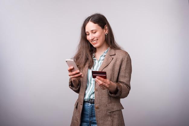 Foto di felice giovane donna in casual utilizzando il telefono mobiel e tenendo la carta di credito.