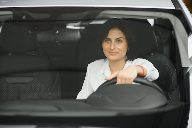 Foto di felice giovane donna seduta all'interno della sua nuova automobile. concetto per il noleggio auto