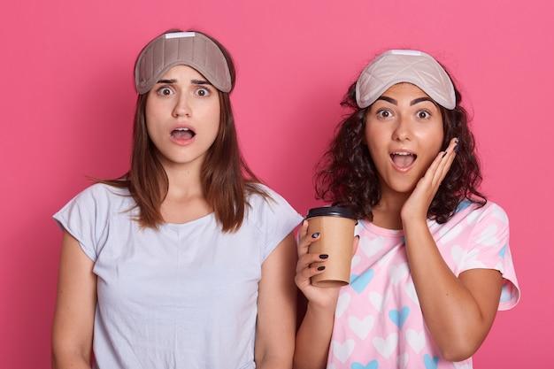 Foto di femmine piuttosto giovani emotive che guardano direttamente tenendo il caffè, aprendo e bocca gli occhi ampiamente, scioccate