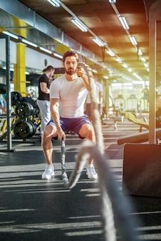 Foto di forte concentrato giovane sportivo uomo che lavora in palestra. usare le corde per il suo allenamento.
