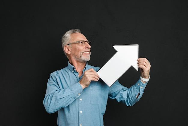 Foto di gentiluomo barbuto anni '60 con i capelli grigi indossando occhiali da vista tenendo in bianco il puntatore a freccia discorso diretto da parte, isolato su muro nero