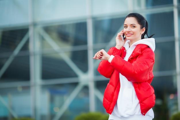 Foto di gioiosa donna fitness anni '30 in abbigliamento sportivo toccando bluetooth earpod e tenendo il telefono cellulare, mentre si riposa nel parco verde