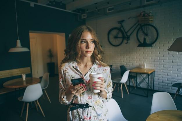 Foto di giovane ragazza bionda carina con una tazza di caffè tenendo il telefono e digitando il testo, bella donna yong con unghie rosa brillante