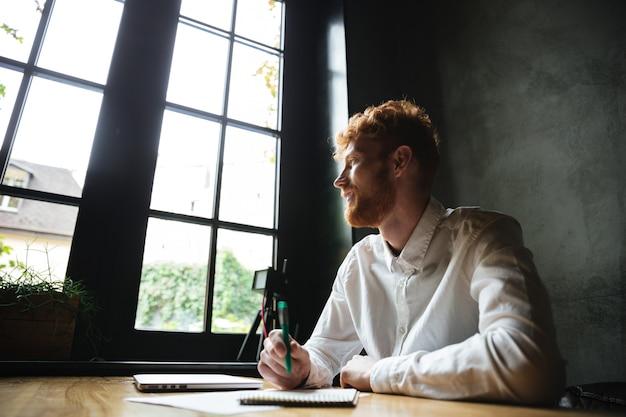 Foto di giovane uomo barbuto readhead bello sorridente seduto sul posto di lavoro a casa, guardando la grande finestra