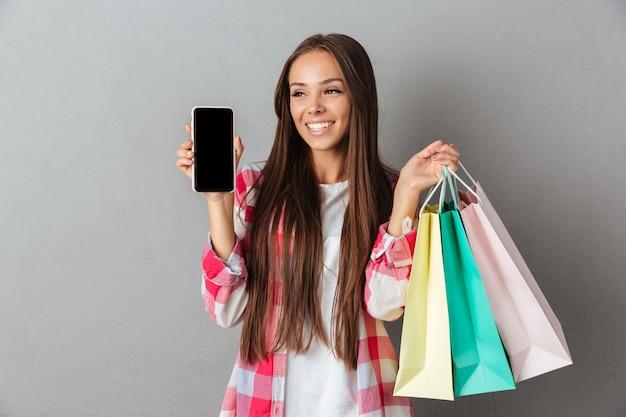 Foto di giovani sorridenti sacchetti della spesa della tenuta castana, mostrando schermo mobile in bianco, distogliente lo sguardo