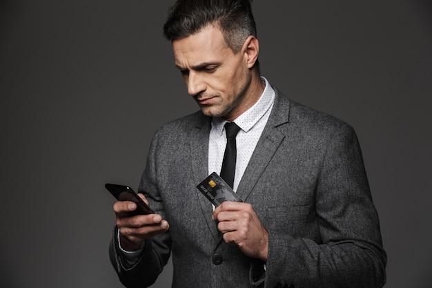 Foto di imprenditore fiducioso uomo in giacca e cravatta che tiene smartphone e carta di credito per il pagamento online, isolato sopra il muro grigio