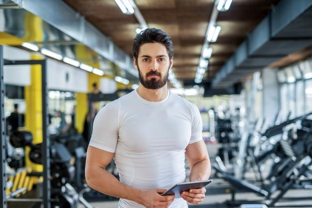Foto di istruttore di fitness personale bello forte in posa davanti alla telecamera in palestra luminosa.