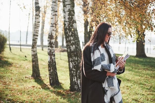 Foto di lato. il giovane castana sorridente in occhiali da sole sta nel parco vicino agli alberi e tiene il blocco note