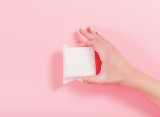 Foto di mani femminili che tengono un assorbente su una rosa