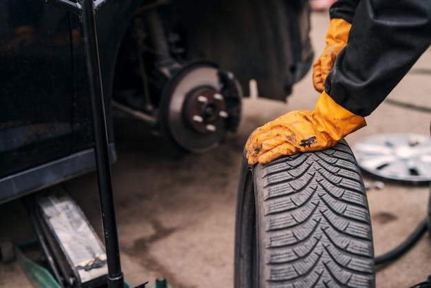 Foto di meccanici auto mani mettendo pneumatici per auto su auto in officina.