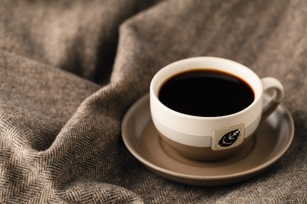 Foto di messa a fuoco selettiva di accogliente sciarpa lavorata a maglia con tazza di caffè e libro aperto. stile retrò filtrato
