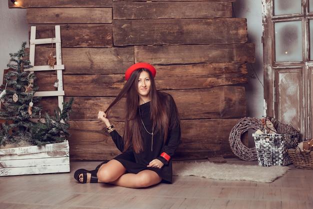 Foto di moda di bella donna con i capelli scuri in elegante abito nero. albero di natale sullo sfondo