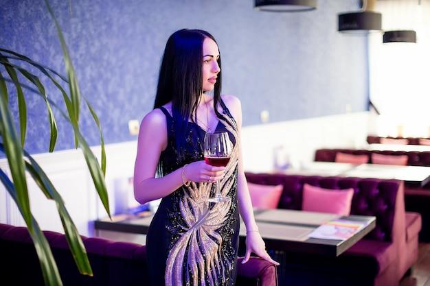 Foto di moda di bella donna sensuale con i capelli ricci in abiti eleganti nella caffetteria, bere la vite