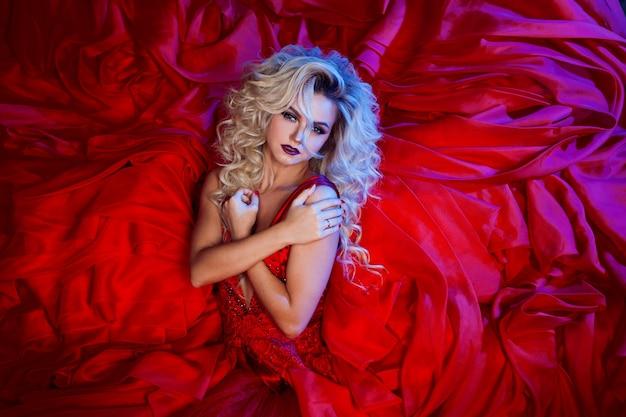 Foto di moda di giovane donna magnifica in abito rosso. ritratto in studio