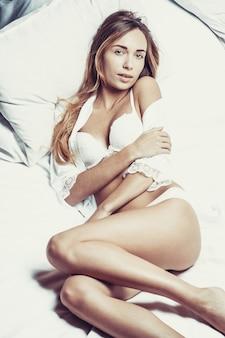 Foto di moda di giovane donna sexy indossando lingerie bianca, corpo stupefacente.