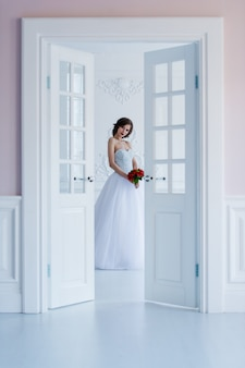 Foto di moda di una bella sposa nella stanza luminosa accanto alle porte