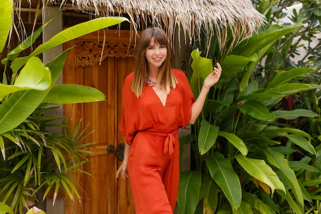 Foto di moda estiva all'aperto di splendida donna in abito boho in posa in un resort di lusso tropicale.
