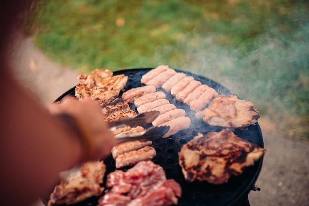 Foto di pov degli uomini che arrostiscono col barbecue carne di pollo